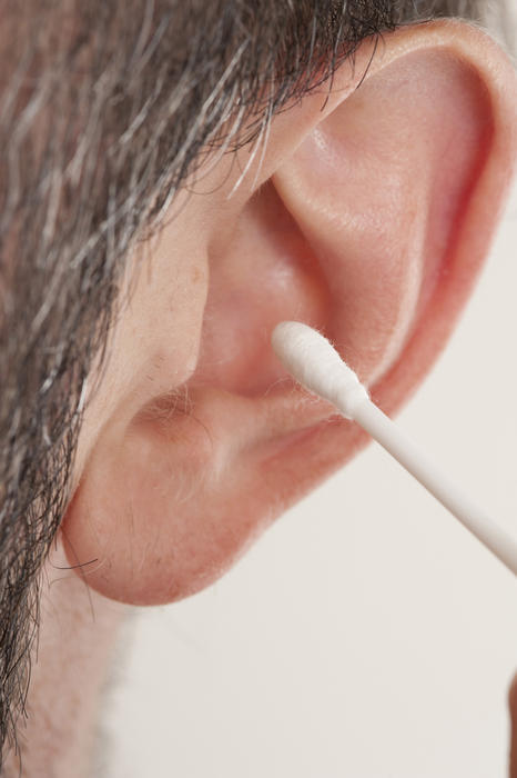 Extreme Macro Close Up of Man Cleaning Ear with Cotton Stick Swab Q-Tip in Studio with White Background