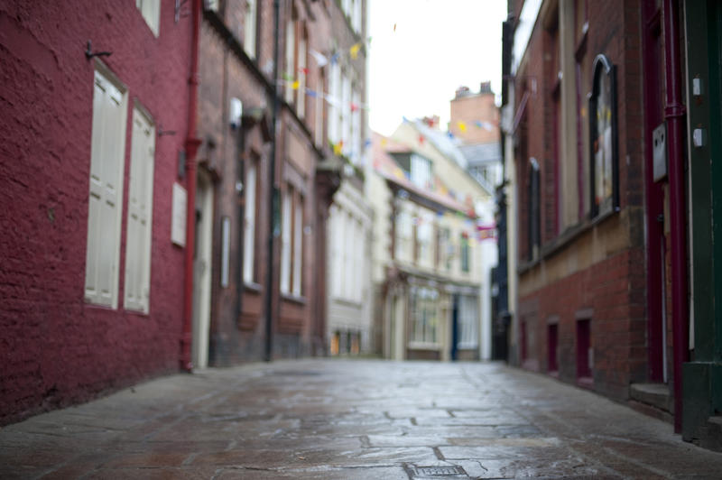 Low angle view of the cobblestones looking down Grape Lane in Whitby lined with traditional old English architecture