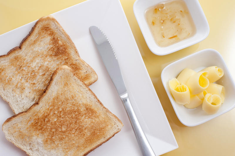 Overhead view of two slices of white toast served with butter coils and marmalade on the side for breakfast