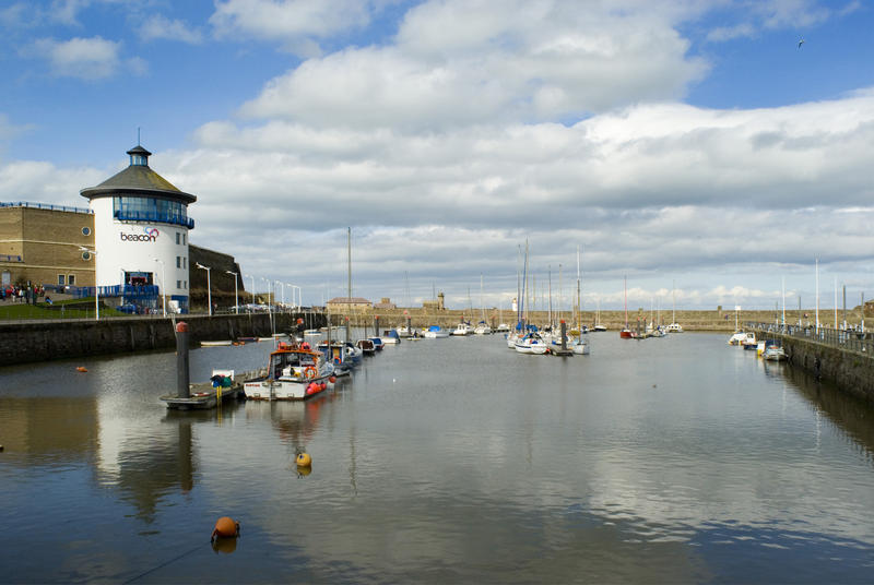 View of an inner basin at Whitehaven harbour with moored fishing boats and the beacon used to guide ships into harbour