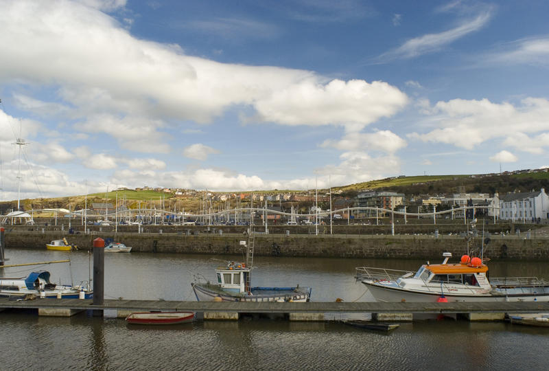 Small fishing craft moored at a wooden jetty in Whitehaven harbour with a view of the waterfront area behind