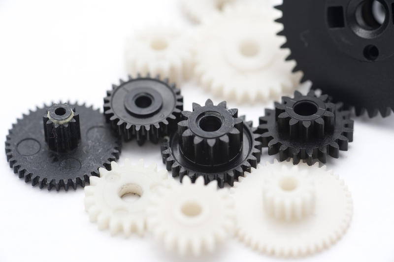Working Together Concept - Close up Black and White Plastic Gear Wheels Isolated on White.