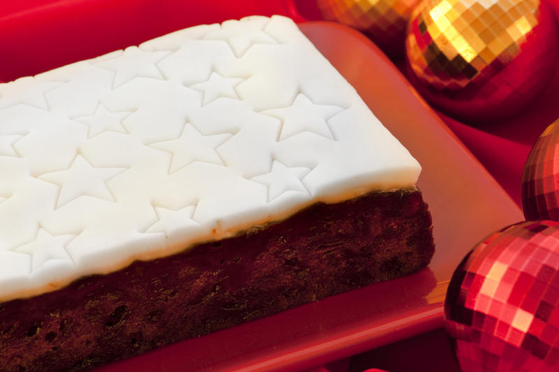 Uncut commercial Christmas fruit cake with a decorative white icing impressed with a pattern of stars on a platter on a festive Christmas table