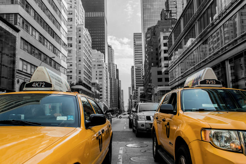 <p>Two yellow cabs in the foreground, with background turned to black and white.</p>