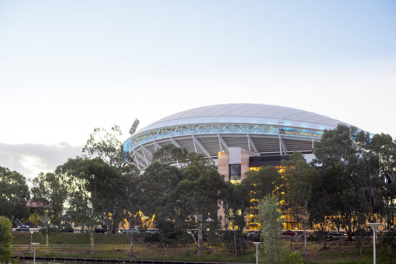 Exterior view of the Adelaide Oval or cricket and sports stadium, South Australia viewed over trees at dusk