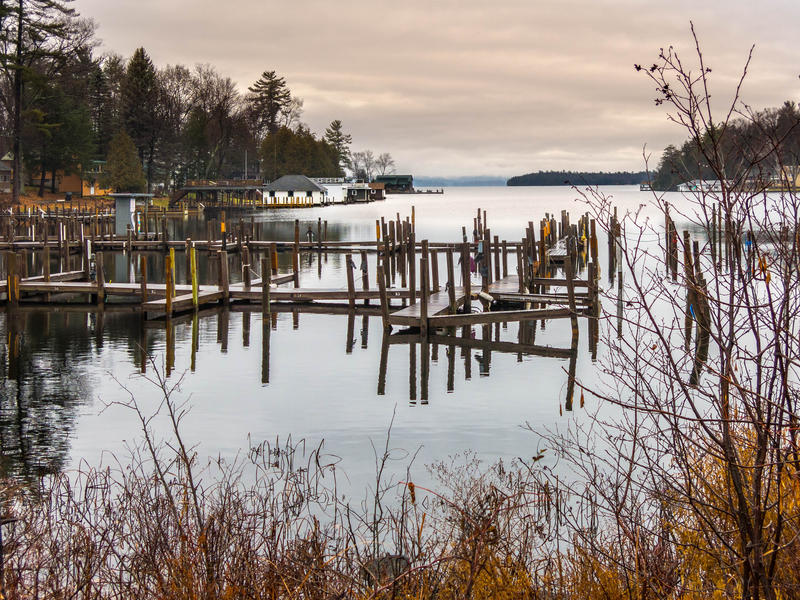<p>The piers with overcast skies and pilons and boat docks on a lake in the Champlain Valley, rural Vermont.</p>