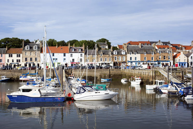 Pleasure Boats Docked in Harbor Lined with Quaint Homes in Village of Anstruther, Scotland on Sunny Day with Blue Sky