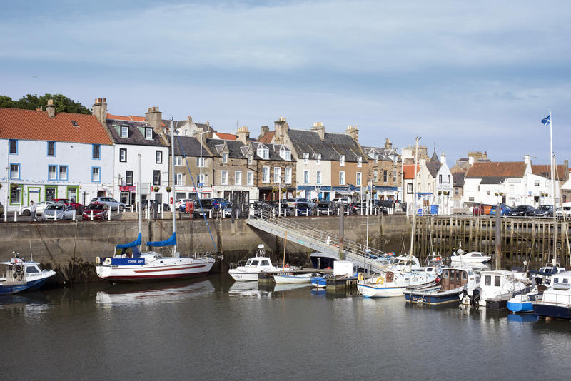 View from across the water of various docked boats at pier in Anstruther, Scotland