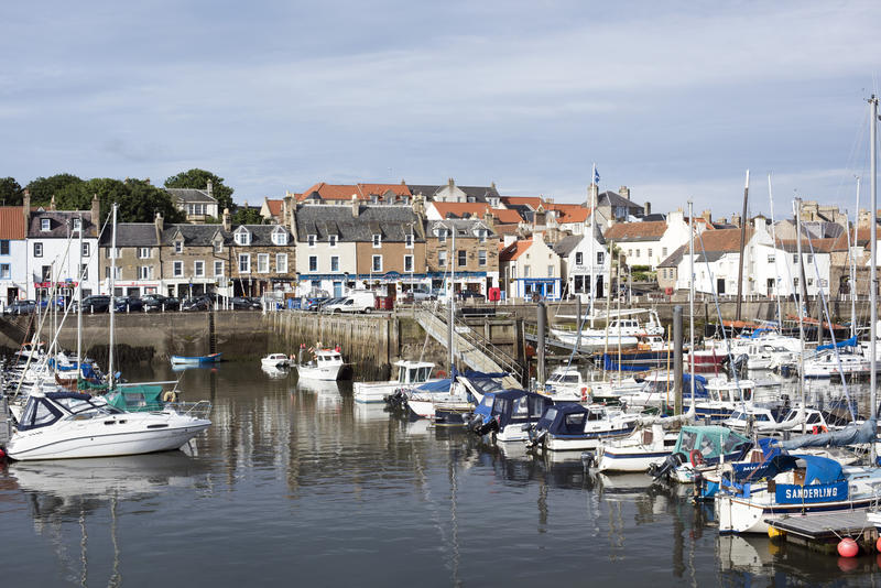 Pleasure and fishing boats moored in Anstruther harbour on the Fife coast of Scotland in a scenic waterfront view