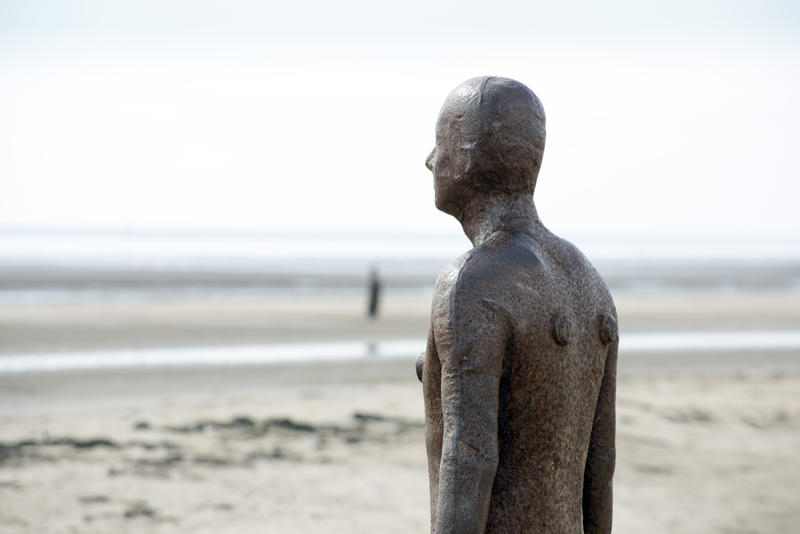 Close up a beach statue from Another Place by Antony Gormley, Crosby, UK facing out towards the ocean with copy space