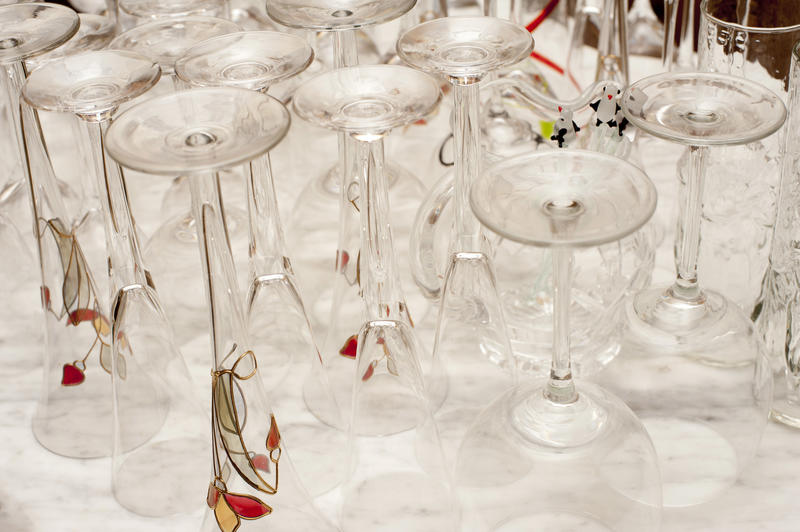 Assorted clean upturned drinks glasses with conical cocktail glasses and wineglasses on a white counter
