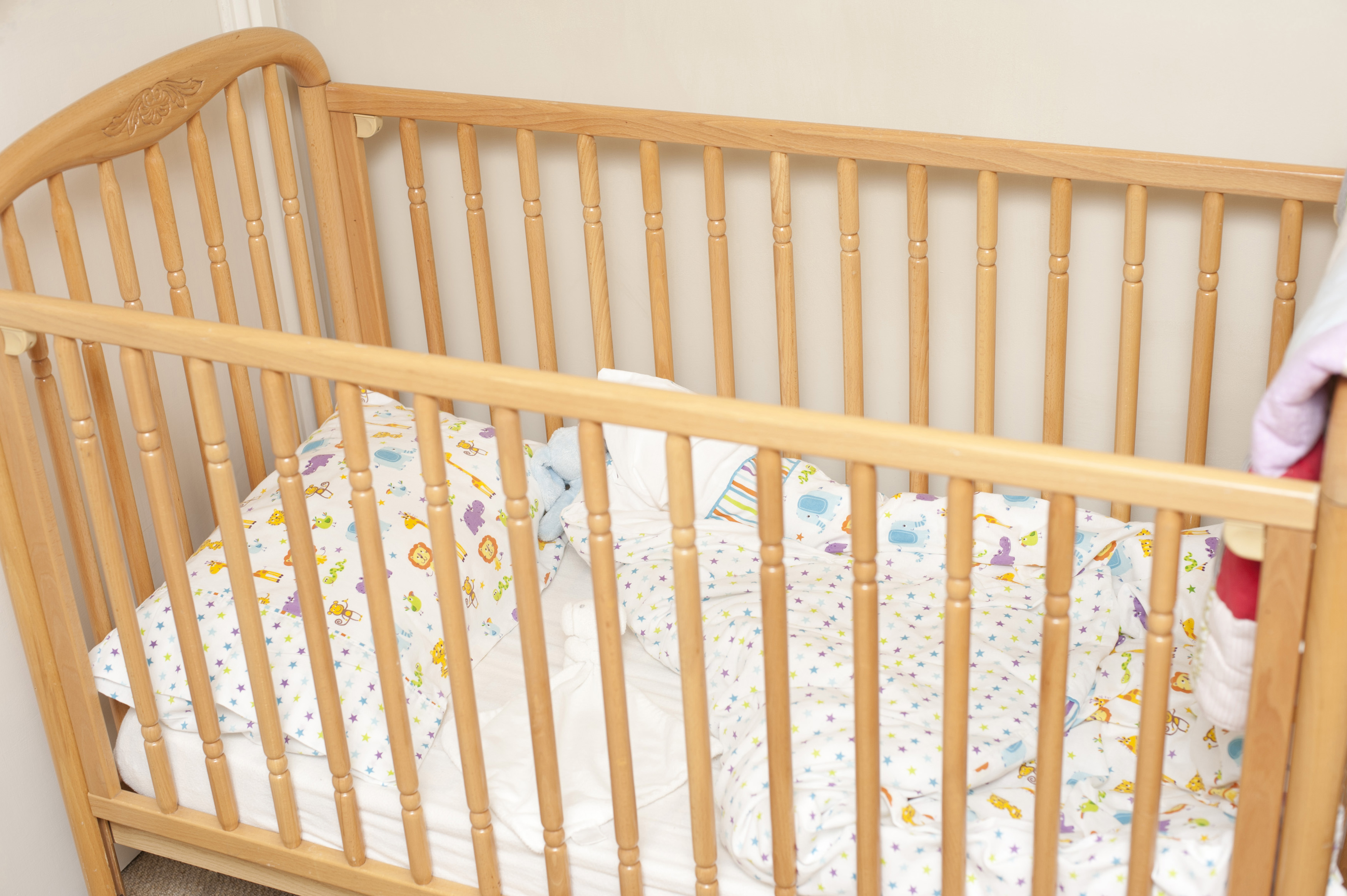 ... Empty Pine Colored Wooden Baby Crib With Folded Over Blanket In Corner .