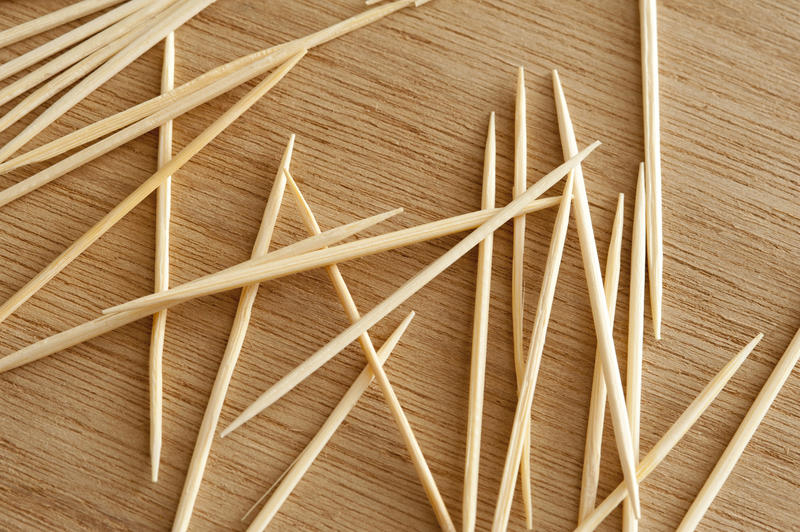 Loose wooden toothpicks or cocktail sticks scattered on a bamboo board in a close up overhead view