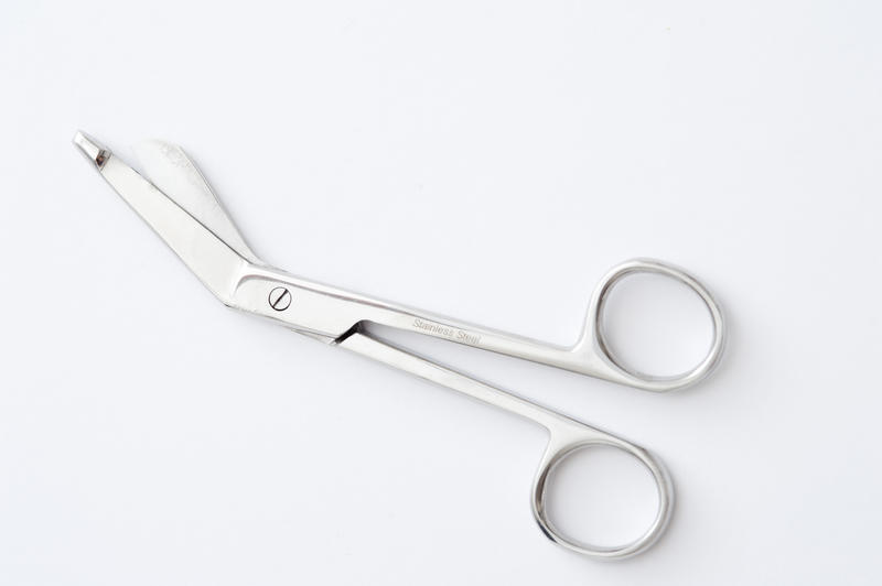 Pair of surgical bandage scissors with angled points to facilitate entering between the skin and fabric when a bandage is in situ on a patient, diagonal view over white