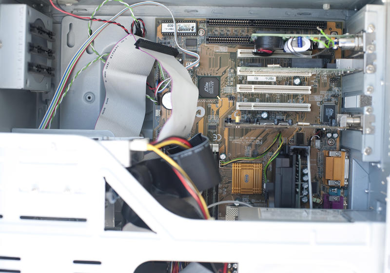 Motherboard installed inside big computer box, close-up image with case metal elements in foreground