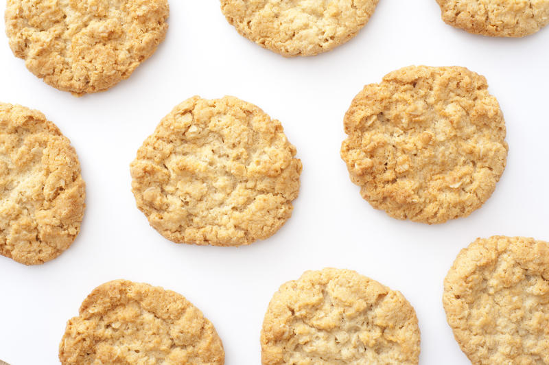 Top down view on cropped white tray with evenly spaced freshly baked round biscuit cookies