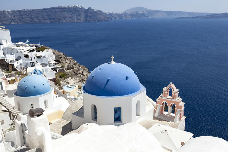 <p>Blue domed churches are a traditional feature of Oia in Santorini and they make a stunning scene against the traditional white buildings.</p>