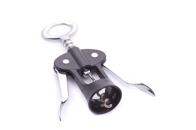 Plastic and metal corkscrew wine bottle opener with levers on white with copy space