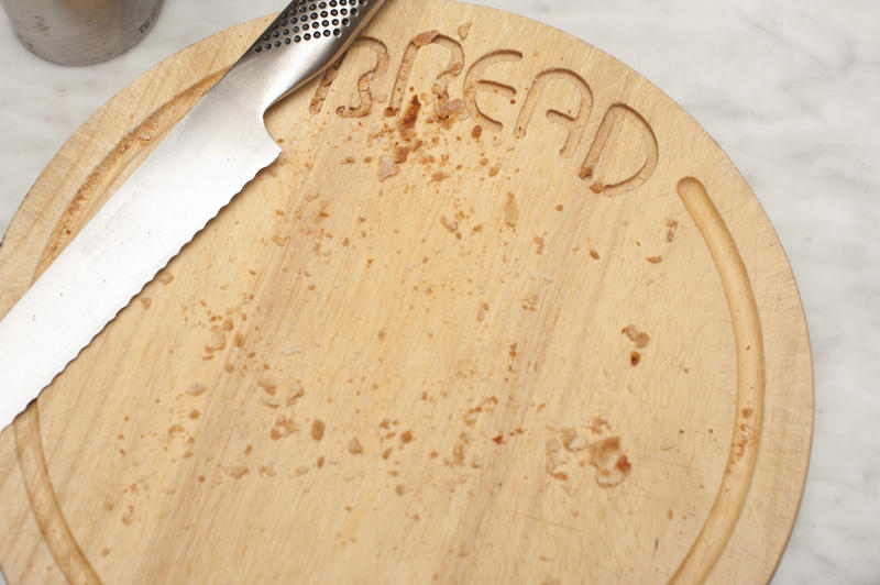 Circular wooden bread board with crumbs and stainless steel knife viewed from above after cutting and serving the bread