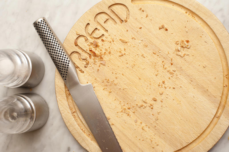 Stainless steel knife and circular wooden bread board with text covered with crumbs after cutting the bread, condiments alongside viewed top down