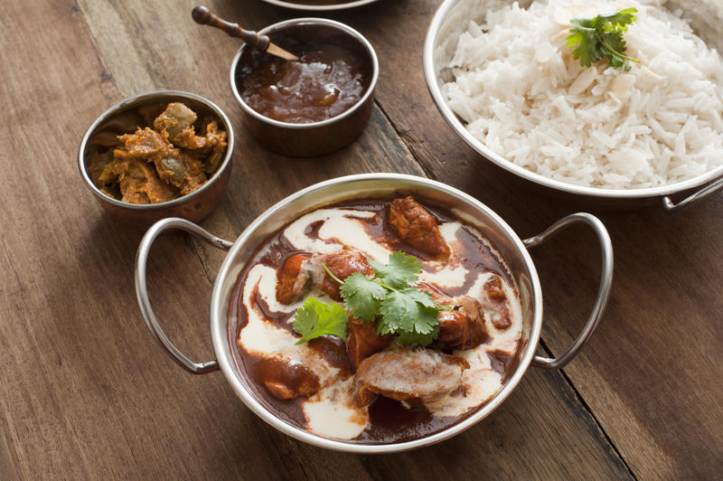 Assortment of delicious Indian cuisine of rice, meat and creamy sauce in metal serving pans on wooden table