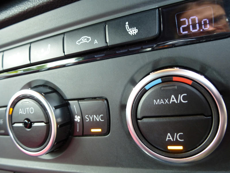 Air conditioner controls on a black car dashboard to control the interior temperature of the vehicle