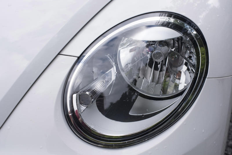 Car headlight unit in a sloping wing on a white car with recessed globe and lens