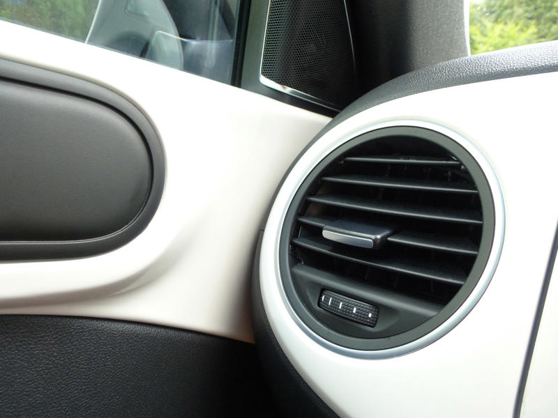 Black side air vent in a white motor car viewed into the corner angle with the door in a travel and transport concept