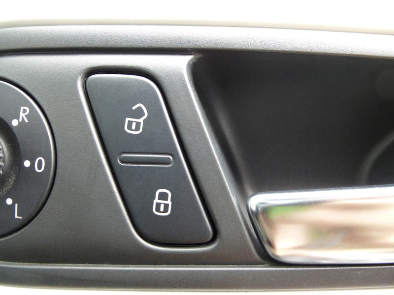 Car window control buttons showing open and closed padlock icons for safeguarding children