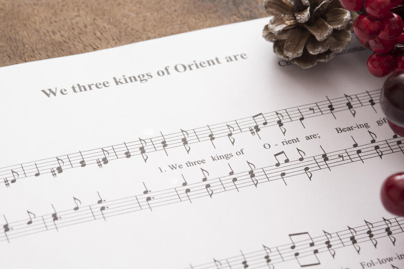 Christmas carol music with berries and pine cone decorations with a close up view of the score for We Three Kings Of Orient Are