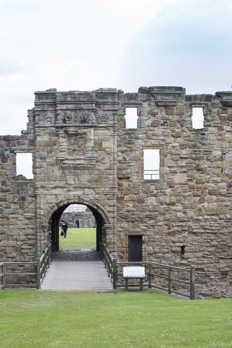 Ruined wall with a Gothic arch at St Andrews Castle, Scotland with people visible through the opening sightseeing on the grass beyond in a travel and tourism concept
