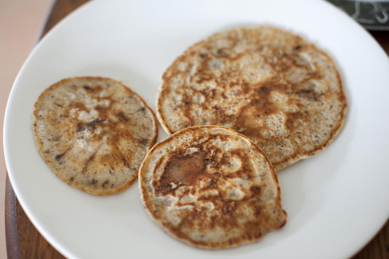 Three homemade fried chocolate chip pancakes served on a white plate in a high angle view