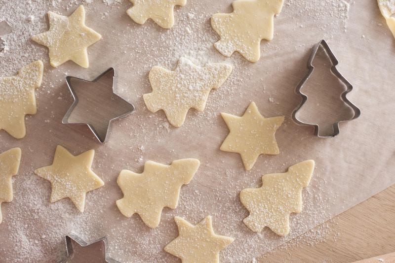 Making Christmas cookies with star and tree shaped cookie cutters in an overhead view of uncooked pastry shapes on oven paper