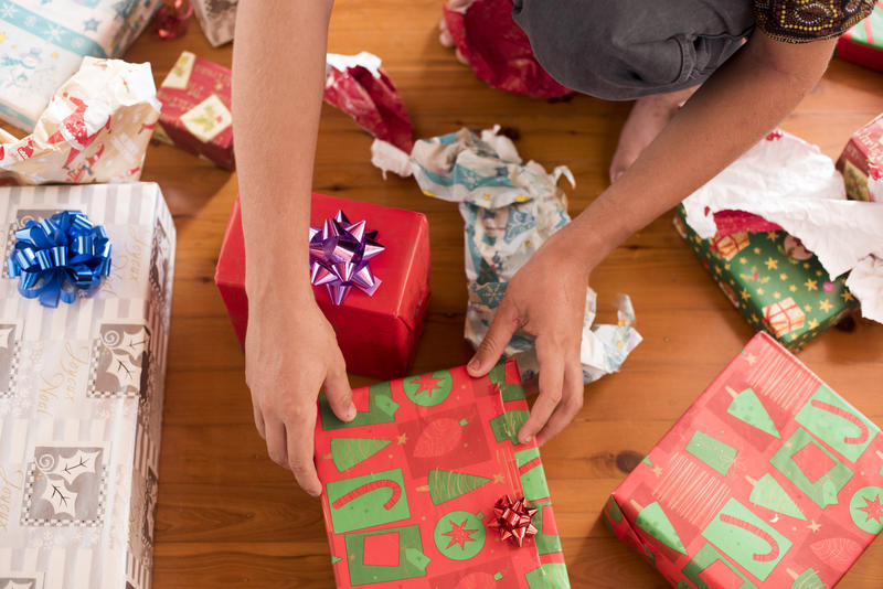 A close up of a teenager unwrapping Christmas presents on a timber floor.