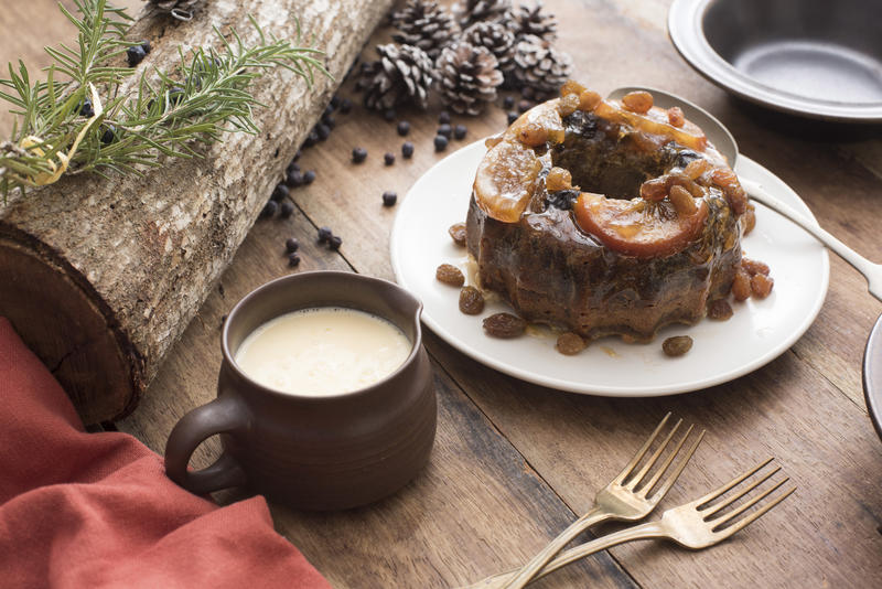 Tasty traditional Christmas plum pudding with fruit and brandy sauce on a decorated rustic table