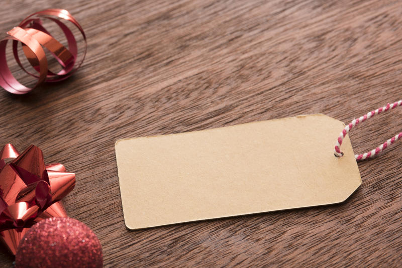 Blank brown gift tag with copy space for your holiday greeting lying on a wooden table with red Christmas decorations