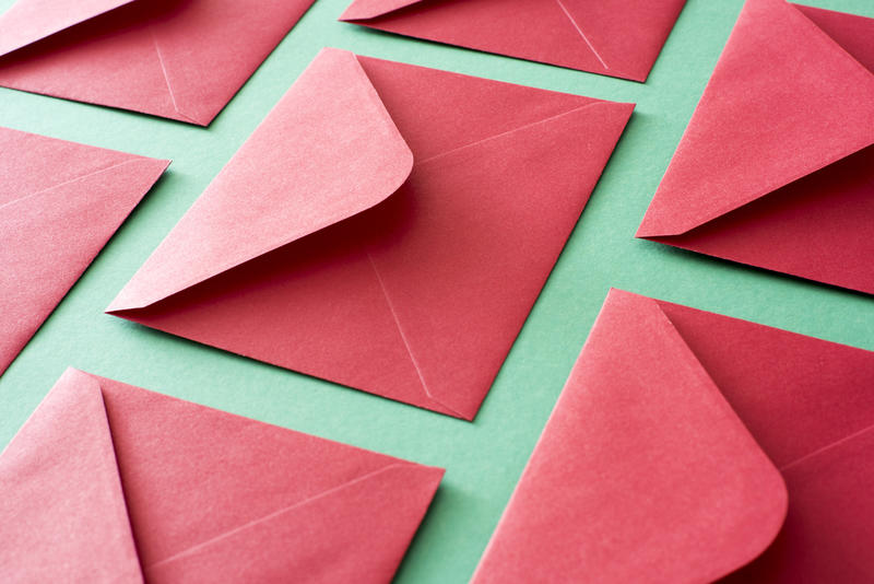 Festive red envelopes for Christmas or Valentines Day lying face down with open flpas on a textured green surface in a full frame diagonal view