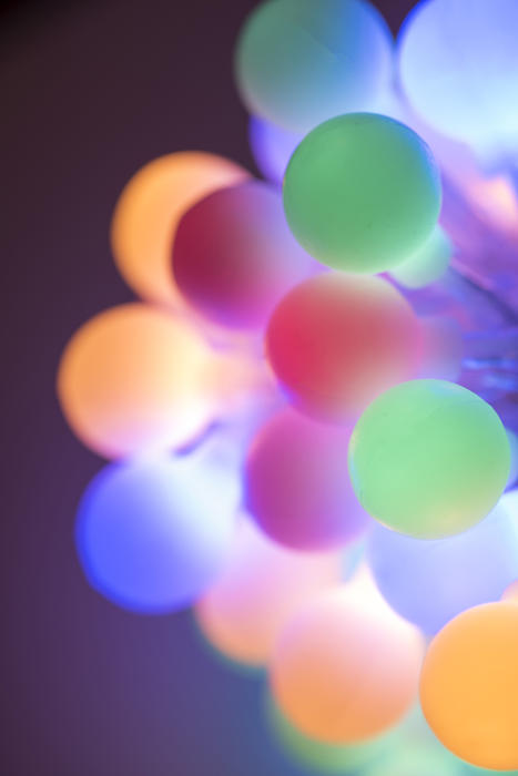 Colorful bundle of glowing round Christmas lights in pastel or muted coors with shallow dof in a festive holiday background