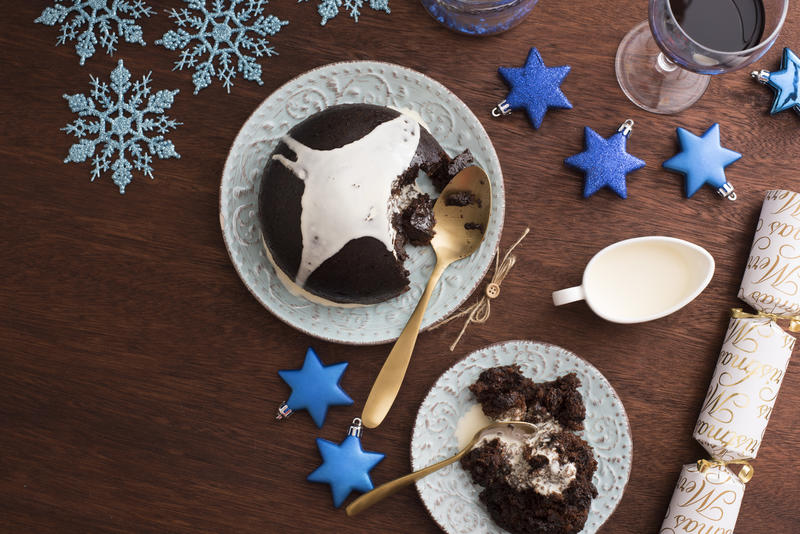Serving Christmas pudding with brandy cream on a festive blue themed table with stars and snowflakes viewed from overhead with a served plate to the side