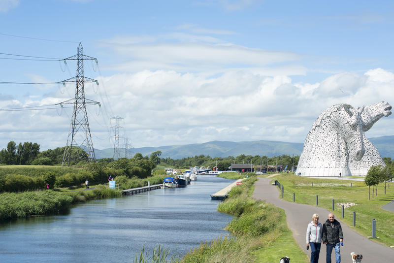 Tourists walking along path at the Kelpies landmark statue of two horse heads near canal in Scotland - not model released