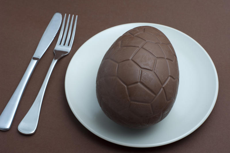 Serving of a chocolate Easter egg for dinner or dessert on a white plate with knife and fork in a conceptual image