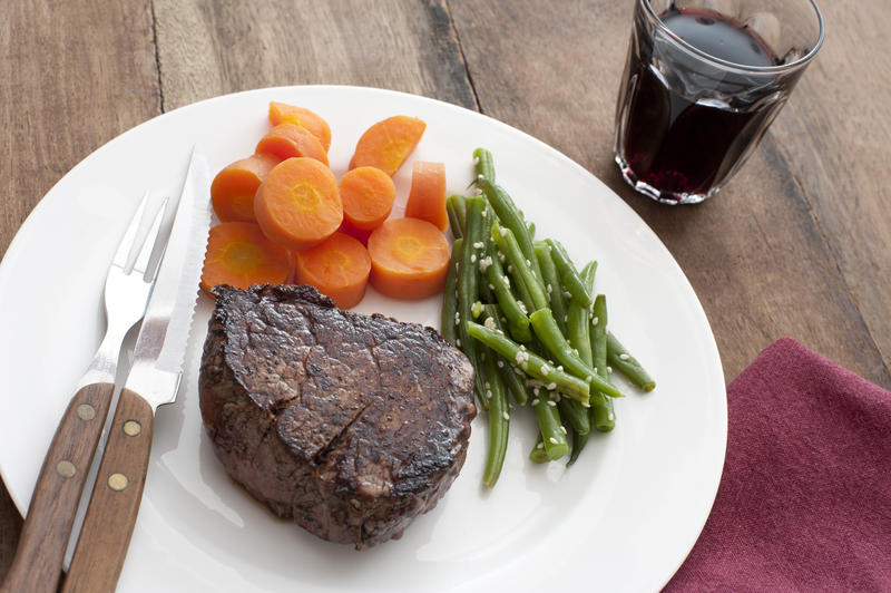 Hearty and healthy dinner of well done ribeye steak besides cooked carrot pieces and seasoned green beans by glass with refreshing beverage