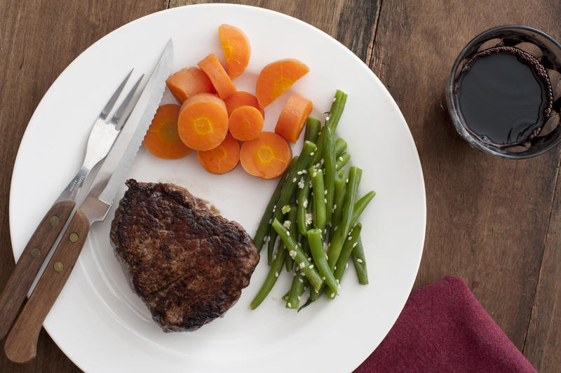 Medallion of grilled fillet steak with fresh vegetables, diced carrots and seasoned green beans, served on a plate with a glass of red wine on the side, overhead view