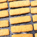 12996   Breaded fish fingers on an baking tray