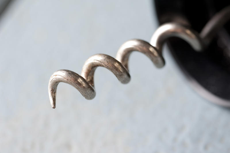 Close up on a steel corkscrew tip on a wine bottle opener over a textured white background with copy space