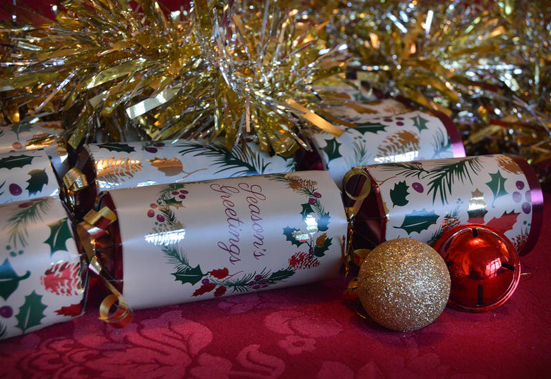 <p>Christmas crackers on a table with ornaments</p>