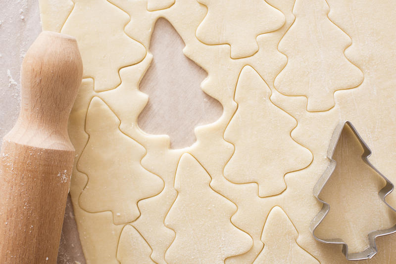 Baking homemade Christmas tree cookies with a close up view of uncooked dough with cut out shapes, a cookie cutter and rolling pin