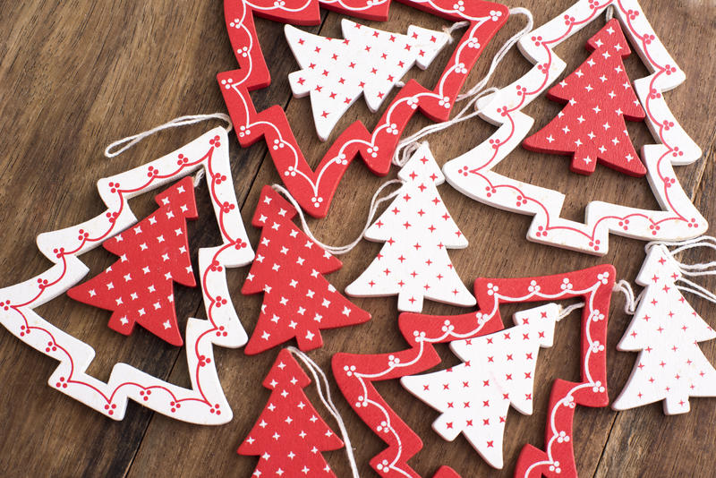 Colorful red polka dot Christmas tree decorations lying ready to be hung on a wooden table viewed high angle