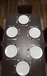 17151   Dark wood dining table laid with clean plates