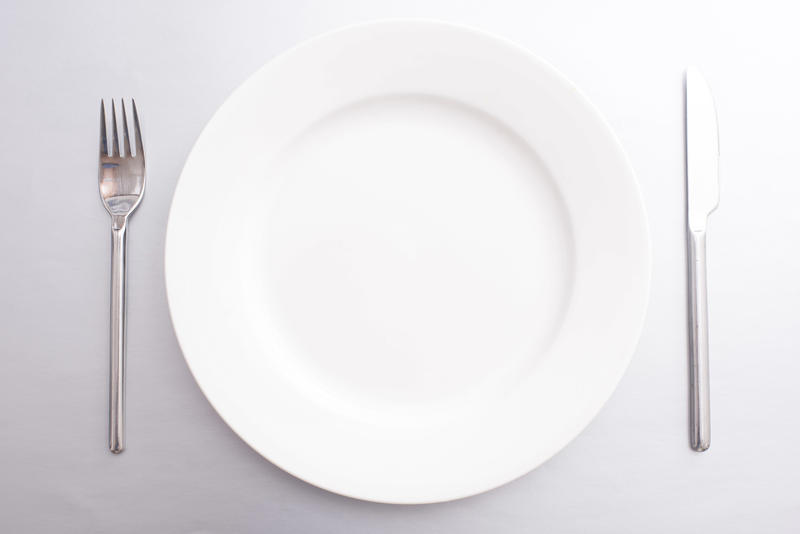 Clean empty white dinner plate with silver metal knife and fork in a simple place setting ready to serve food